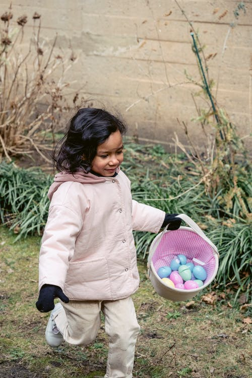 Hispanic girl walking outside in warm clothes and gloves with basket full of colorful plastic Easter eggs