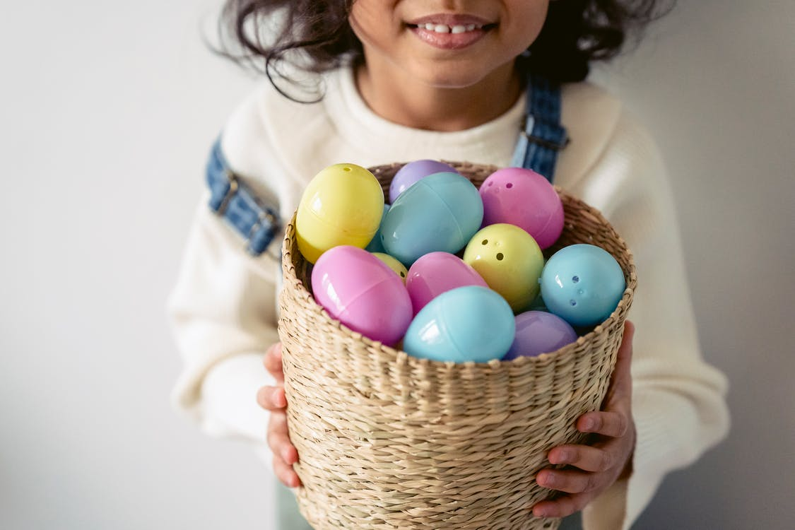 Crop unrecognizable child with colorful Easter eggs in wicker basket