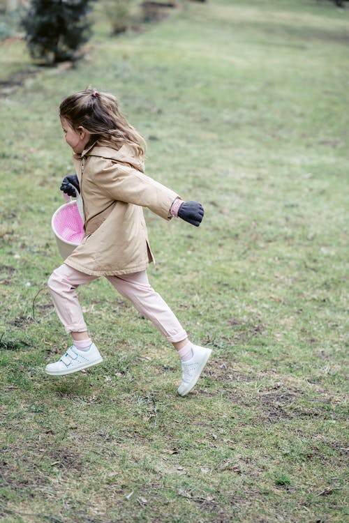 Full body side view of cute little girl in warm bright coat with pink bucket running on green grass
