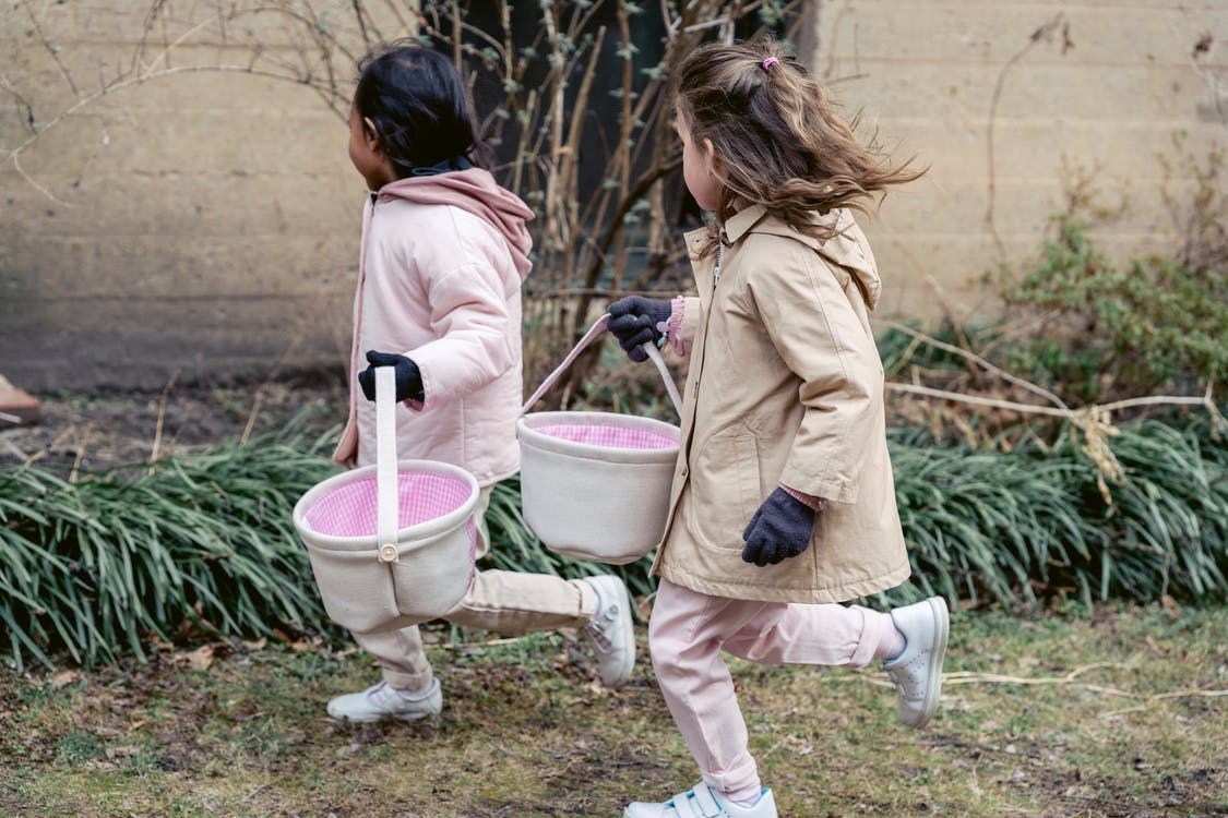 Side view of little multiracial children in warm coats with toy buckets running outside