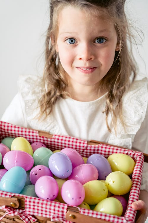 Fair haired little girl with container full of colorful plastic Easter eggs looking at camera