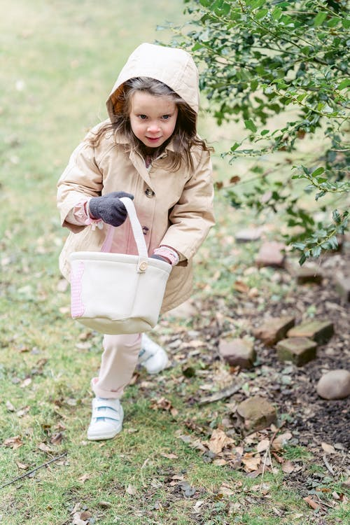 Little fair haired girl in warm bright coat and sneakers with toy bag walking on grass near tree outdoors