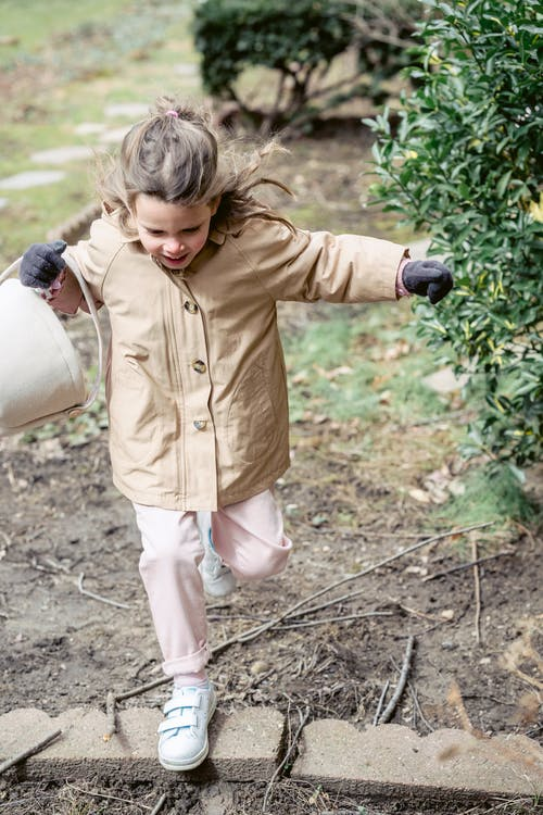Full body of fair haired girl in bright coat and white sneakers with toy bucket walking near shrub