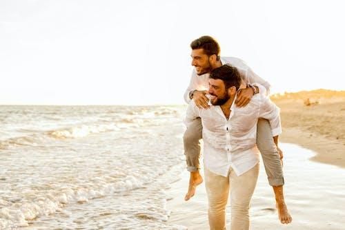Man in White Dress Shirt Kissing Woman in White Dress on Beach