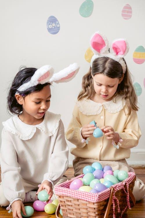 Cute diverse girls in bunny ears on heads sitting near Easter eggs