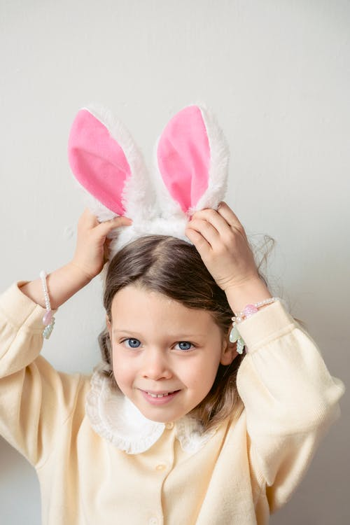 Adorable preschool girl in casual wear with bunny ears headband looking away while standing on white background in light room