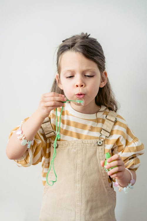 Adorable preschool girl with bracelets on hands wearing casual outfit blowing soap bubbles while standing on white background in light room