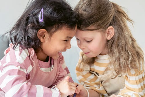 Cute multiethnic preschooler girls making gesture with fingers as sign of friendship forever while playing together in kindergarten
