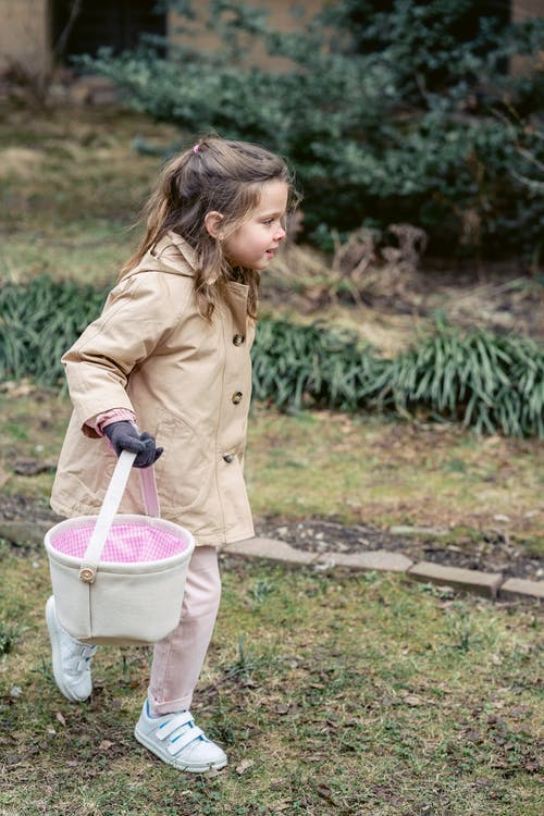 Full body side view of happy little girl in warm coat carrying Easter bucket while searching for eggs during traditional game in spring garden