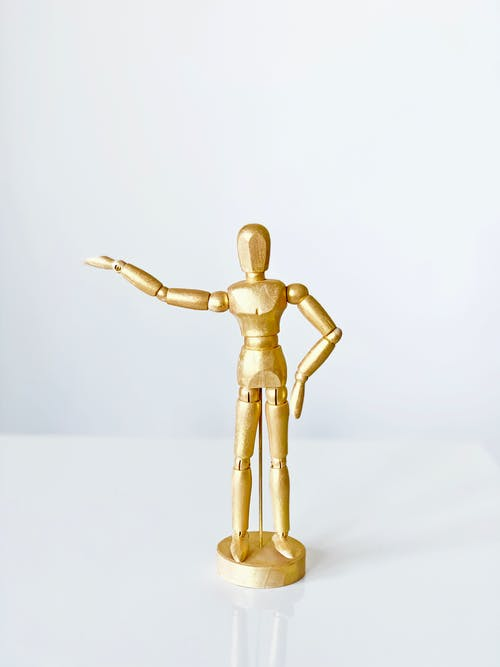 Gold Human Figurine on White Table