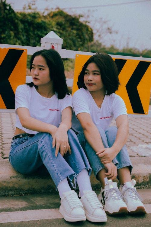 Girls in White Crew Neck T-shirt Sitting on the Roadside