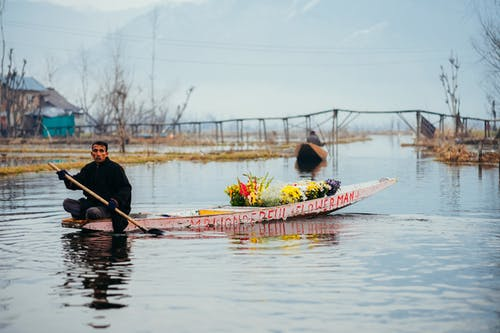 Man Rowing a Boat with Flowers on a River