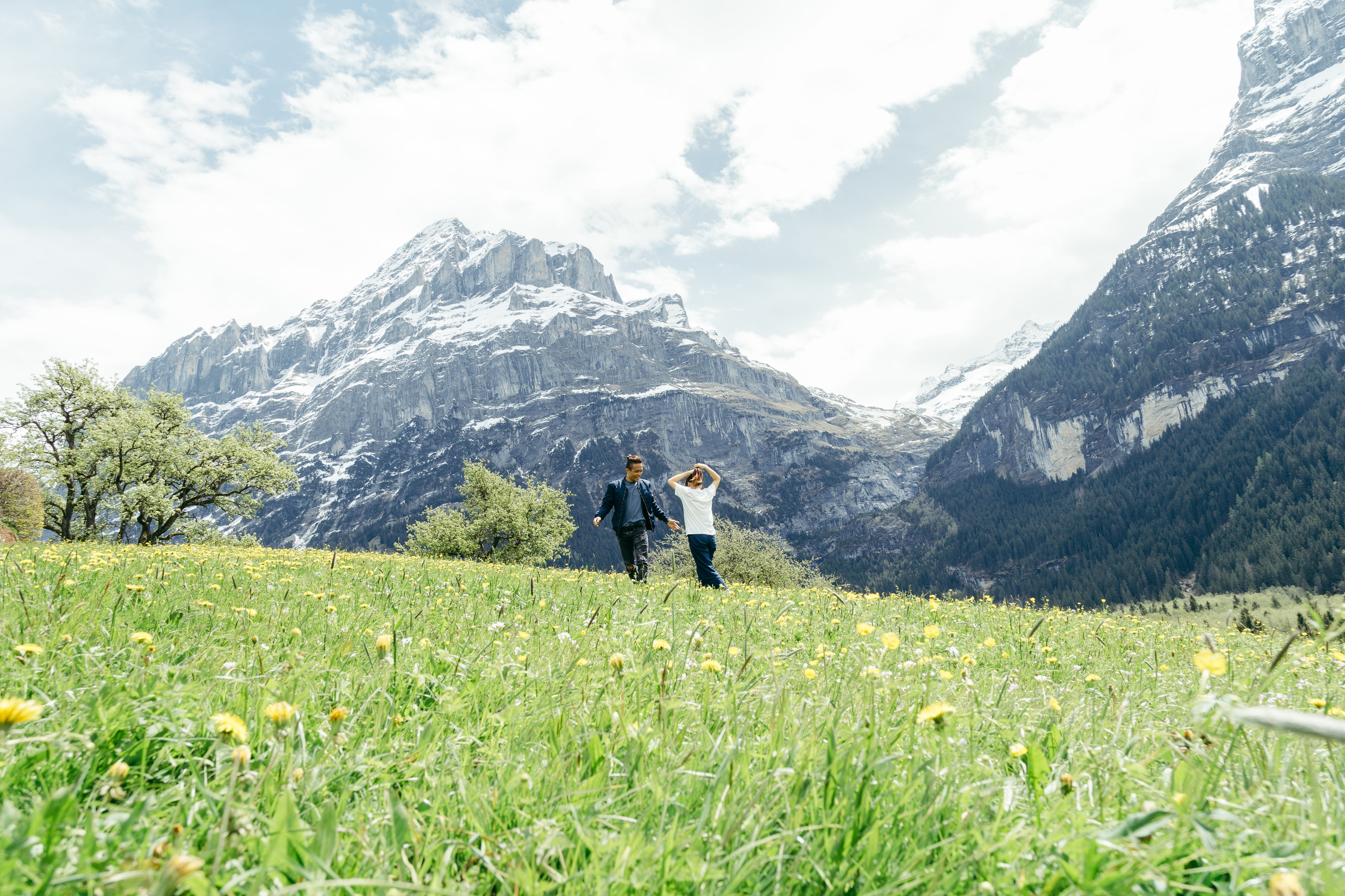 Man and Woman Walking on Meadow of Yellow Flowers