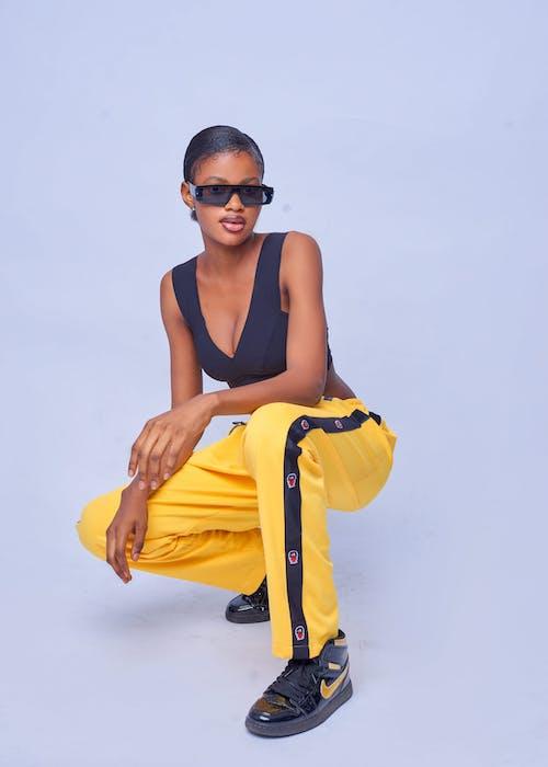 Stylish black woman hunkering in studio