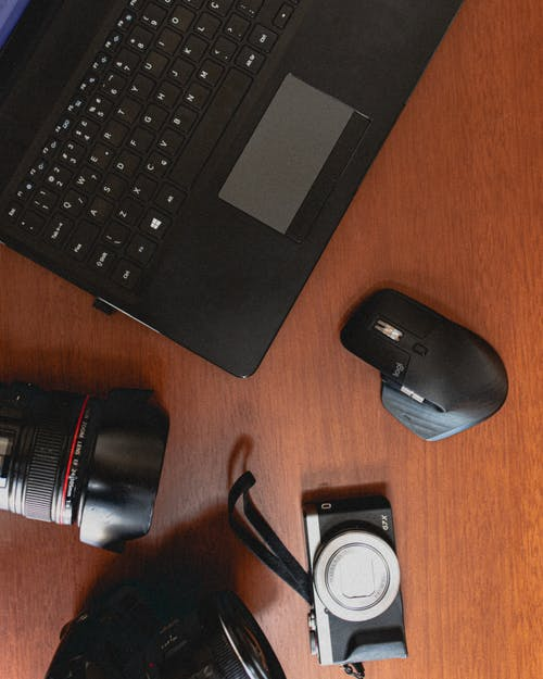 Contemporary laptop and photo camera with lens on table
