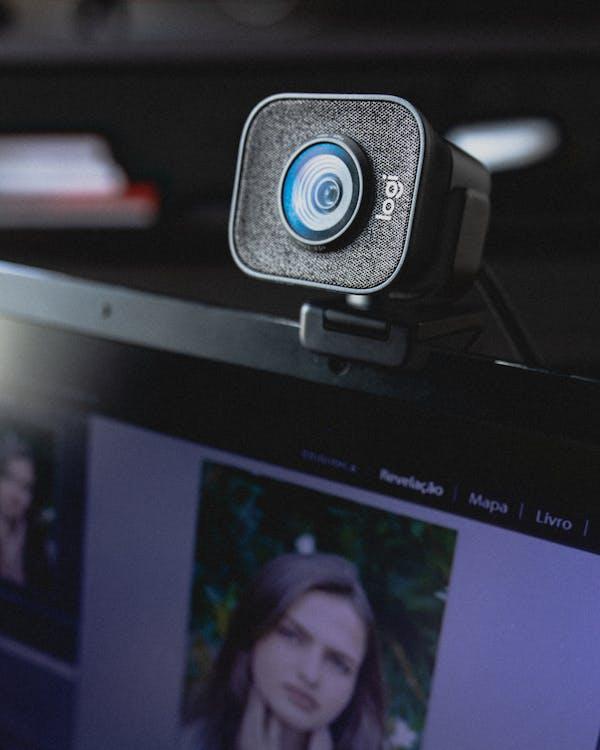 Modern video camera hanging on display of laptop
