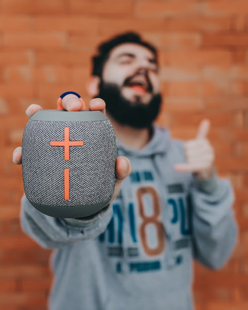 Soft focus of portable speaker in hand of bearded man singing song while listening to music