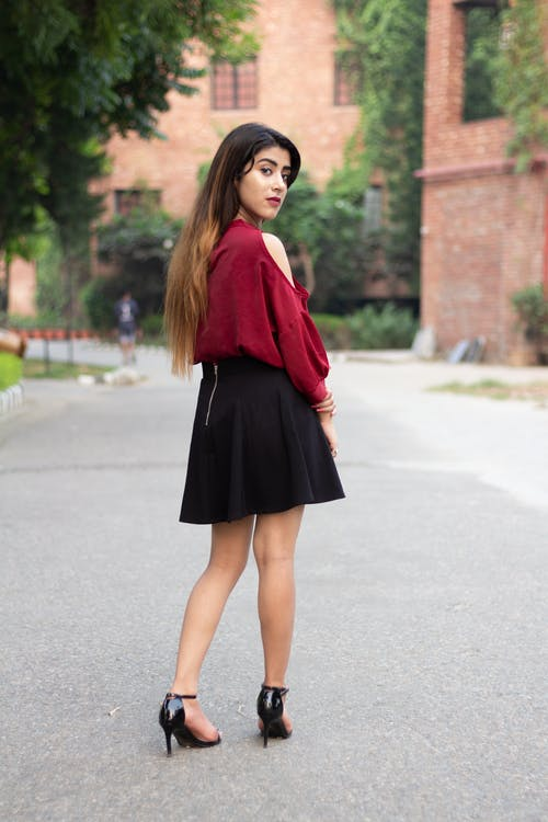Woman in Red Long Sleeve Shirt and Black Skirt Standing on Gray Concrete Road