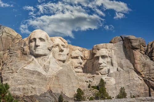 Faces Curved on a Rocky Mountain Side Under a Blue Sky