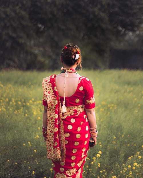 Woman in Red and Yellow Floral Dress Standing on Green Grass Field