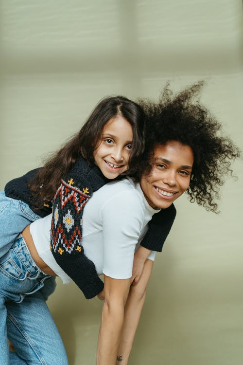 Woman in White Shirt Carrying the Girl on her Back