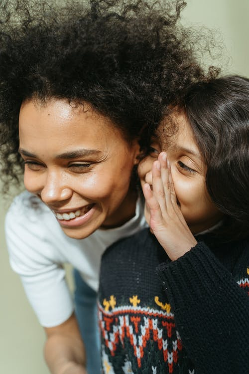 Child in a Black Jacket Whispering to a Woman in White Shirt