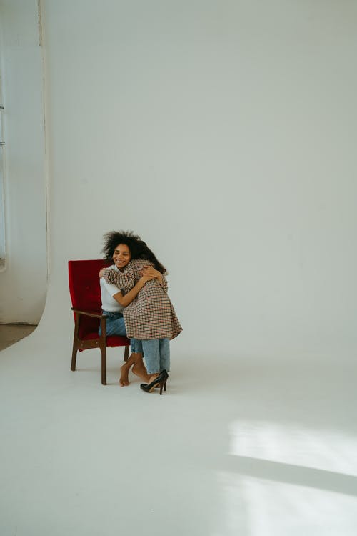 Woman Hugging a Child while Sitting on a Chair
