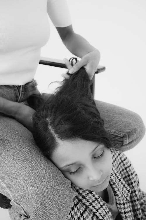 A Person Holding a Child's Hair on her Lap