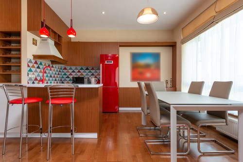 Interior of modern spacious kitchen with bright elements and large dining table in apartment