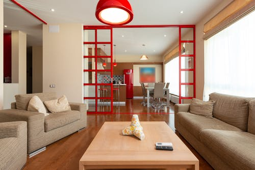 Comfortable sofa and armchair placed near table in living room in modern apartment in daytime