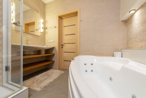 Interior of modern bathroom with shower near bath and sink on cabinet under mirror next to door