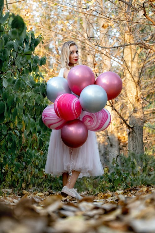 Girl in White Dress Holding Pink Balloons