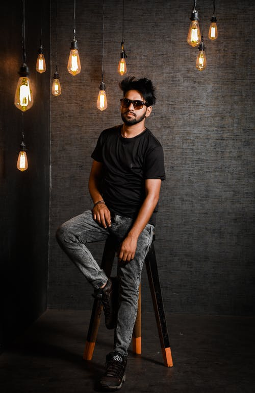 Man in Black Crew Neck T-shirt and Blue Denim Jeans Sitting on Brown Wooden Seat