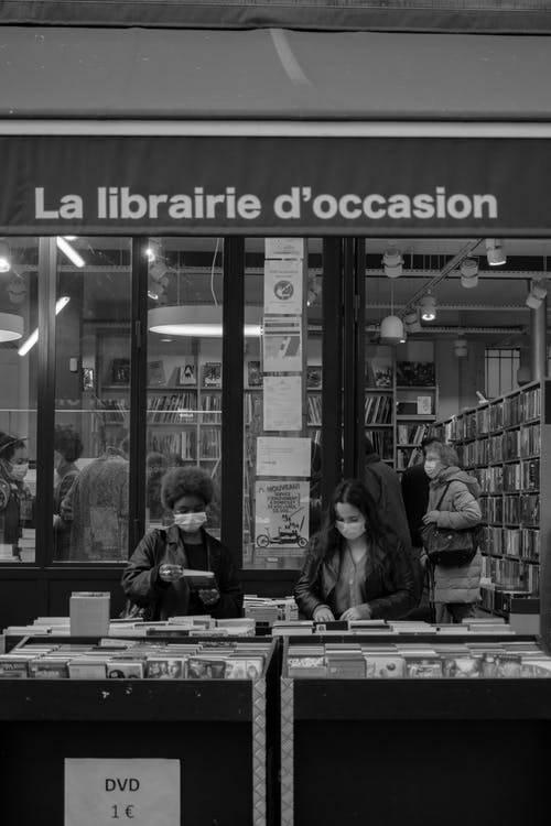 Grayscale Photo of Women Searching for Books in the Bookstore