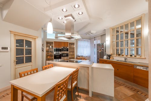 Open kitchen with counter and chairs near cupboards