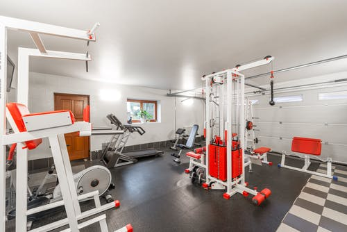 Modern interior design of new spacious fitness gym for home sport training and heavy weightlifting in garage of big house