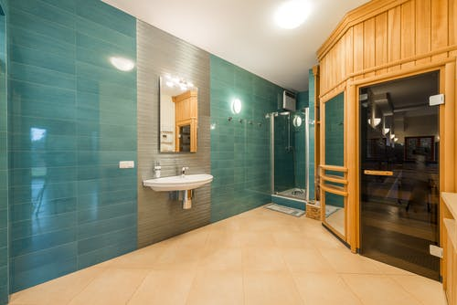 Interior of light shower room with glass cabin and sink and wooden entrance to sauna room with glass doorway