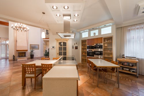 Interior of dining area of modern spacious open plan kitchen with wooden furniture and illuminated lamps on ceiling