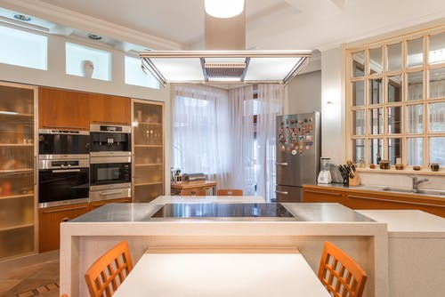 Interior of contemporary kitchen with wooden cabinets and built in appliances and island counter with stove top illuminated with bright lamps