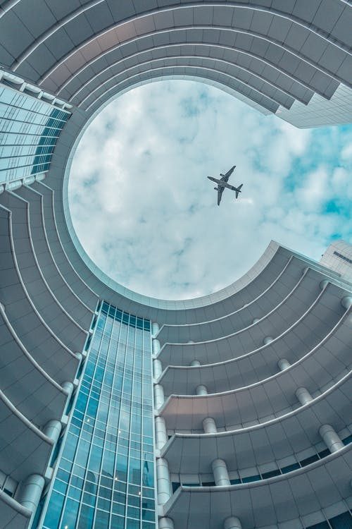 Airplane Flying Over the Circular Building