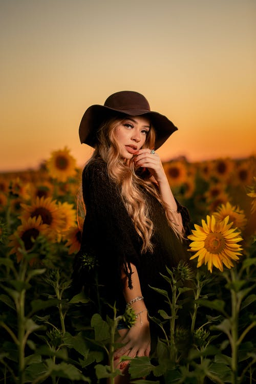 Woman in Black Long Sleeve Shirt Standing on Sunflower Field during Sunset