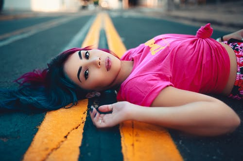 Girl in Pink T-shirt Lying on Yellow and Blue Concrete Floor