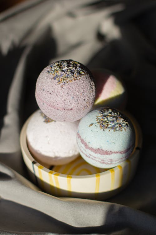 Composition of fragrant pastel bath bombs in shape of balls placed in bowl on gray cloth