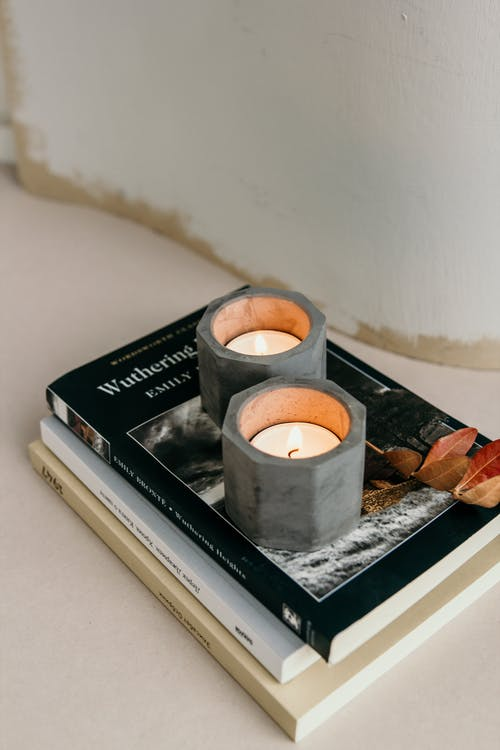 Composition of burning tealights in candleholders placed on stacked books on white surface