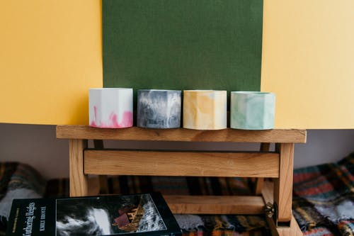 Collection of multicolored candle holders on wooden stand