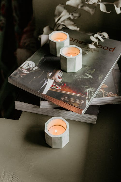 Burning candles in holders on stack of books