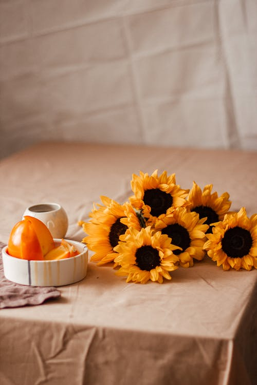 Blooming sunflowers near plate with slices persimmon