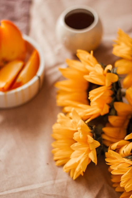 Bunch of blooming sunflowers with lush buds placed on table near bowl with chopped ripe persimmon and coffee