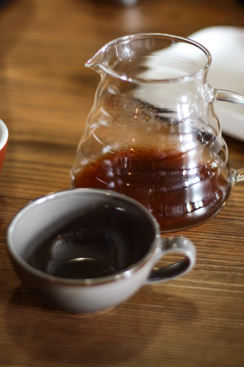High angle of ceramic cup with hot tea in kettle placed on wooden table