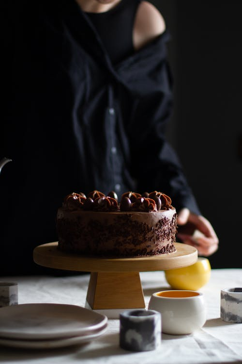 Crop anonymous female standing at table with sweet chocolate cake and plated near candle holders